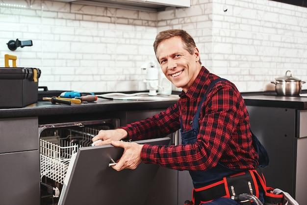 식기 세척기 근처에 앉아서 웃는 전문 남성 기술자에게 전화하십시오.