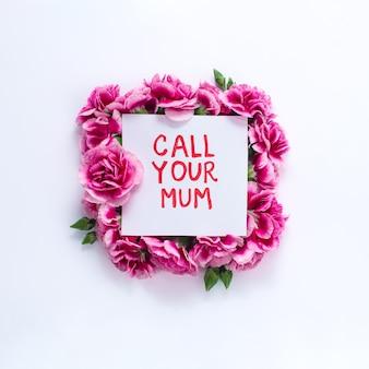 白い背景の上のピンクの花で囲まれた白い紙にあなたのお母さんのテキストを呼び出す
