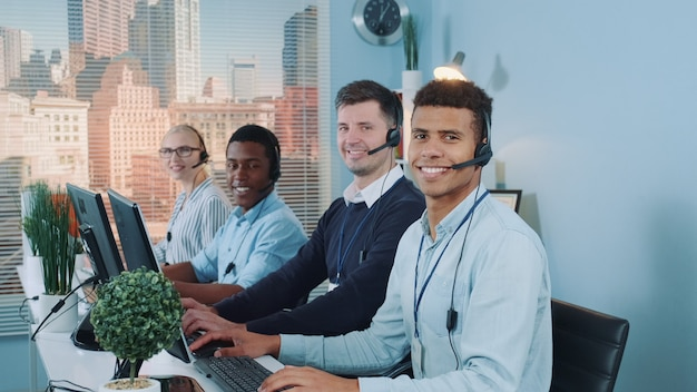 Разнообразная команда клиентов call-центра смотрит в камеру и улыбается