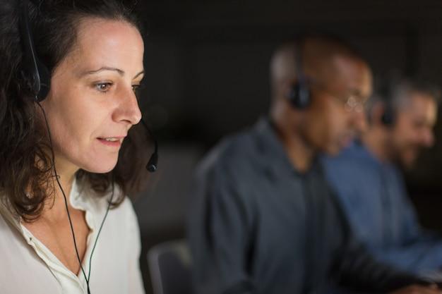 Веселый зрелый оператор call-центра смотрит на экран ноутбука