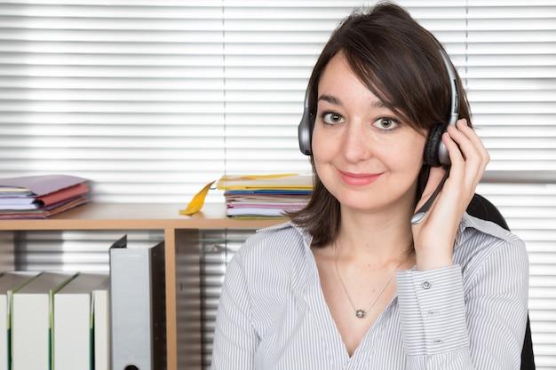 Молодая бизнес-леди на телефоне в офисе в callcenter