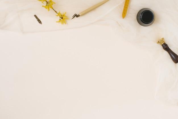 Каллиграфия, острое перо, тушь, перья, старинные принты, цветок форзиции и воск на бежевом фоне с копией пространства