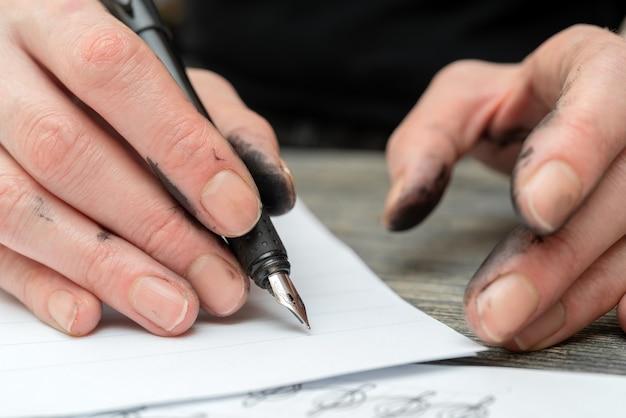 Обучение каллиграфии. перьевая ручка в запачканных чернилами руках.