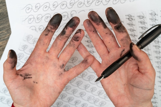 Calligraphy training. fountain pen in ink-stained hands.