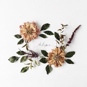 書道の言葉秋とラウンドフレームの花輪パターン、ベージュの乾燥した牡丹の花、枝と葉は白で隔離