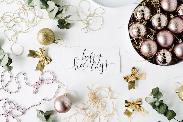서예 단어 해피 홀리데이 및 크리스마스 공, 반짝이, 활, 유칼립투스와 함께 크리스마스 장식으로 만든 프레임.