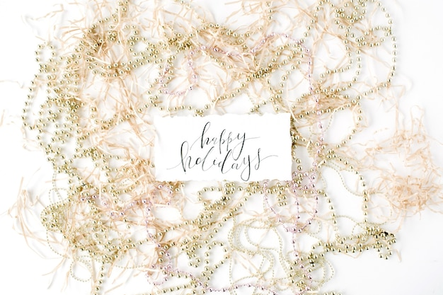 Calligraphy words happy holidays and christmas tinsel decoration.