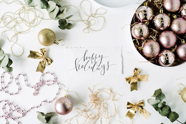 Calligraphy words happy holidays and frame made of christmas decoration with christmas balls, tinsel, bow, eucalyptus.