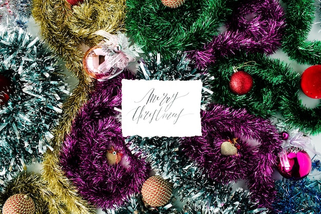 Calligraphy words merry christmas and christmas decoration with colored glass balls, tinsel, toys. flat lay, top view
