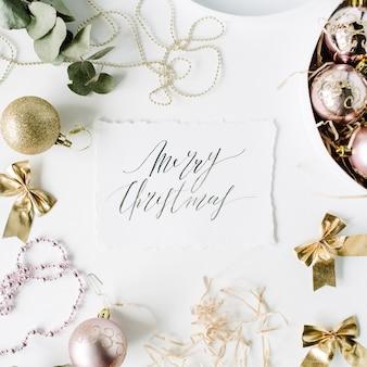 Calligraphy words merry christmas and frame made of christmas decoration with christmas balls, tinsel, bow, eucalyptus.