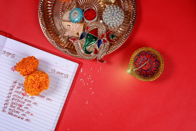 Calligraphy writing in hindi shubha labh means goodness & wealth, over red accounting note book , diya,