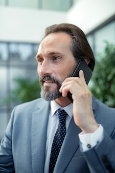 ビジネスパートナーに電話します。彼のビジネスパートナーを呼び出す灰色のジャケットを着てひげを生やしたハンサムな成熟した男