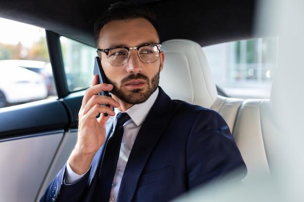 Звонок деловому партнеру. занятый красивый бизнесмен звонит своему деловому партнеру, сидя в машине
