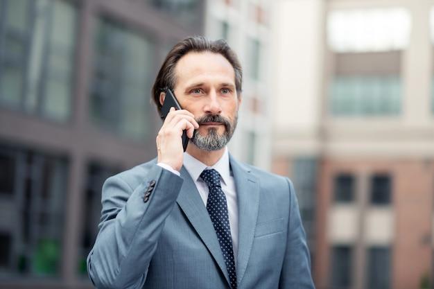 ビジネスパートナーに電話します。彼のビジネスパートナーを呼び出すネクタイを身に着けているハンサムなひげを生やしたビジネスマン
