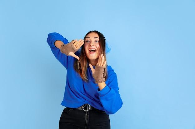 Chiamando. ritratto della donna caucasica su sfondo blu studio. bello modello femminile in vestiti caldi. concetto di emozioni umane, espressione facciale, vendite, annuncio. atmosfera invernale, periodo natalizio, vacanze.