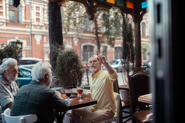 ウェイターを呼んでいます。パブの外に座っている間ウェイターを求める白髪のひげを生やした男