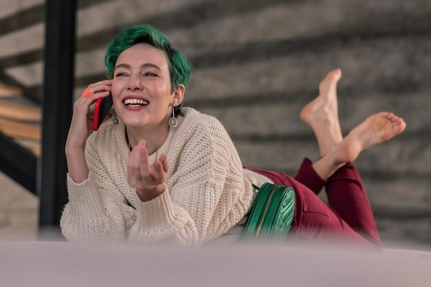 友達を呼んでいます。緑髪の有名なファッション デザイナーが友達に電話してディナーに招待する