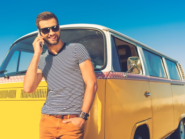 Звоню друзьям. счастливый молодой человек разговаривает по мобильному телефону и держит руку в кармане, опираясь на ретро-мини-фургон