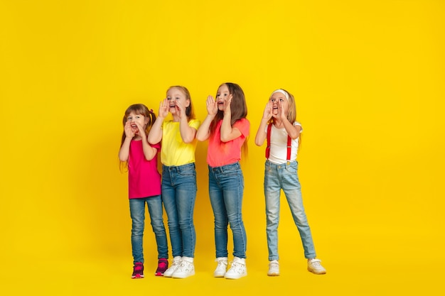 Calling. happy children playing and having fun together on yellow studio wall.