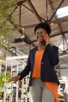 Calling her colleague. dark-skinned office worker calling her colleague while having question