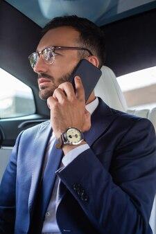 Вызов его секретаря. успешный молодой бизнесмен носить ручные часы, вызывая своего секретаря
