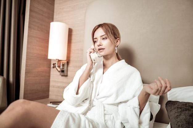 Вызов обслуживания номеров. светловолосая красивая женщина в красивых серьгах звонит в обслуживание номеров