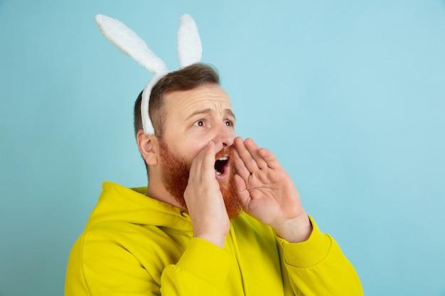 Звонок, крик. кавказский человек как пасхальный кролик с яркой повседневной одеждой на синем фоне студии.