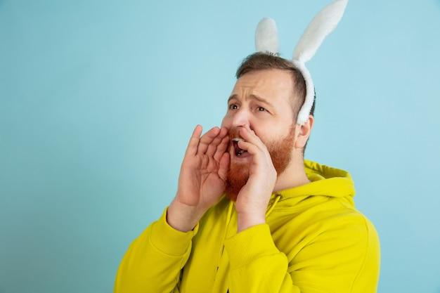 Chiamando, urlando. uomo caucasico come un coniglietto di pasqua con abiti casual luminosi su sfondo blu studio.