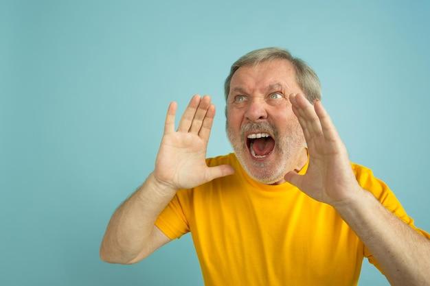 呼び出し、叫びます。青いスタジオの背景に分離された白人男性の肖像画。黄色いシャツのポーズで美しい男性モデル。