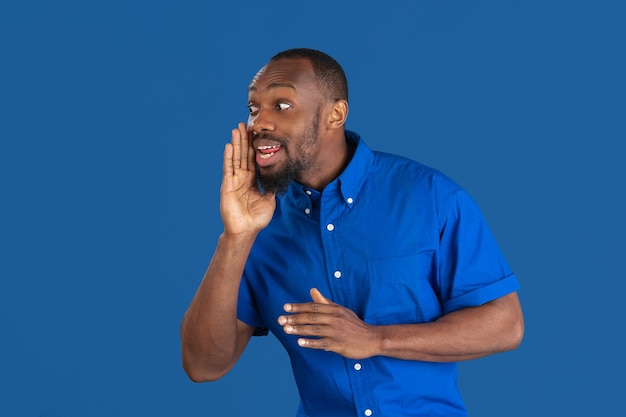 Calling, shouting. monochrome portrait of young african-american man isolated on blue studio wall.