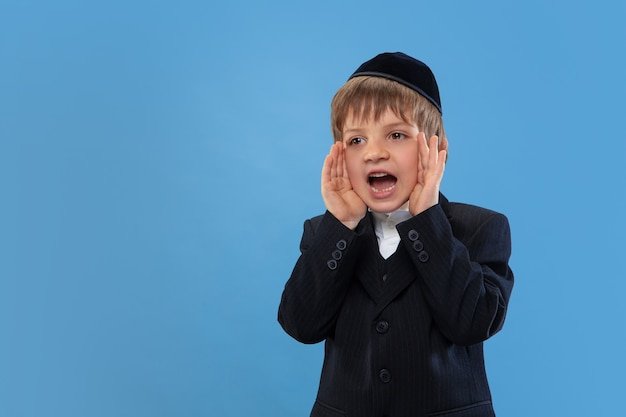 Calling, shouting. portrait of a young orthodox jewish boy isolated on blue wall. purim, business, festival, holiday, childhood, celebration pesach or passover, judaism, religion concept.