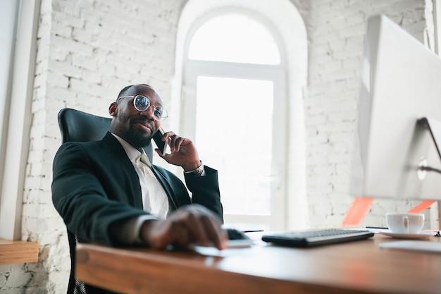전화, 전화 통화. 아프리카 계 미국인 기업가, 사업가 작업 사무실에 집중. 세리오스, 바쁘고 고전적인 정장을 입고 보입니다. 일, 금융, 비즈니스, 성공, 리더십의 개념.