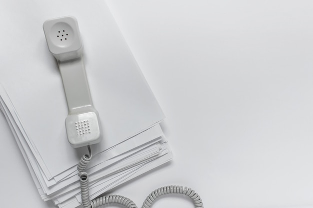 Calling vintage telephone with office papers