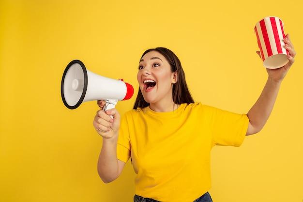 Звонок с попкорном. кавказская женщина на желтой стене. красивая женская модель брюнет в непринужденном стиле. концепция человеческих эмоций, выражения лица, продаж, рекламы, copyspace.