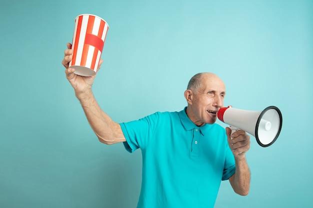 Звонок во рту. портрет кавказского старшего человека на синем фоне студии. красивая мужская эмоциональная модель. понятие человеческих эмоций, выражения лица, продаж, благополучия, рекламы. copyspace.