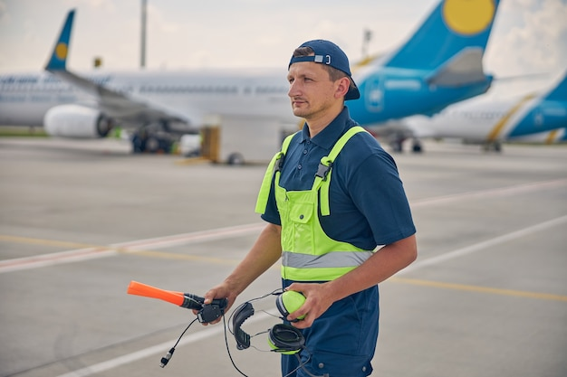 Calm aircraft marshaller with wands and a headset in his hands standing at the airdrome