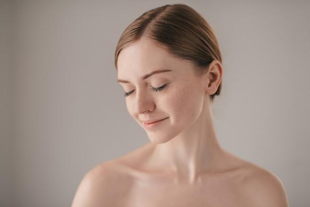 Спокойно и красиво. портрет рыжей женщины с веснушками с закрытыми глазами и улыбкой, стоя на сером фоне
