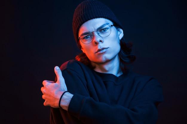 Спокойно и тихо. студия снята в темной студии с неоновым светом. портрет серьезного мужчины.