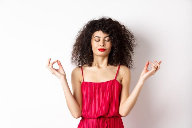 빨간 드레스에 조용하고 편안한 웃는 여자, 눈을 감고 명상, 요가 연습 젠 포즈, 흰색 배경에 서.