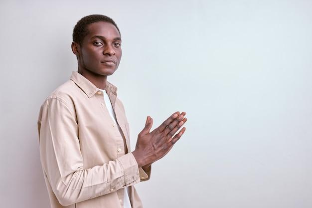 Спокойный и мудрый темнокожий мужчина держит руки вместе, думает и выглядит уверенно. изолированные белые стены студии. вид сбоку