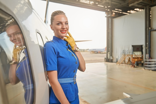 Calm attractive flight attendant touching her chin with a hand in glove and smiling while standing in a hangar