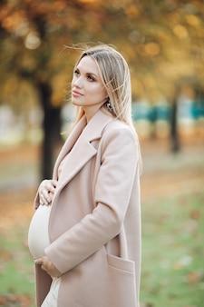 落ち着いた魅力的な妊婦さんが、秋の日はお腹を優しく抱きしめて遠くを見つめます。母性の概念