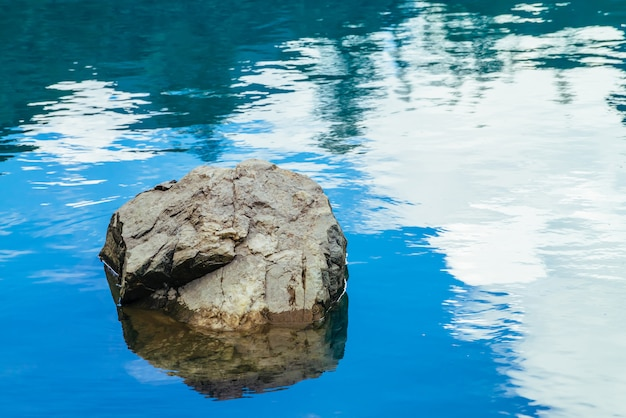 Calm azure clean water surface with big stone