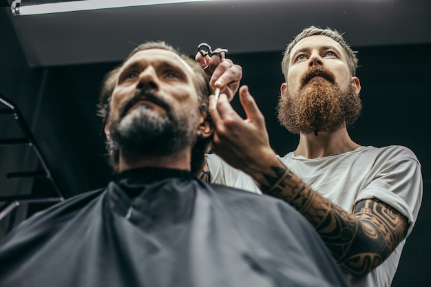 Спокойный бородатый мужчина сидит и смотрит, пока профессиональный парикмахер осторожно подстригает волосы