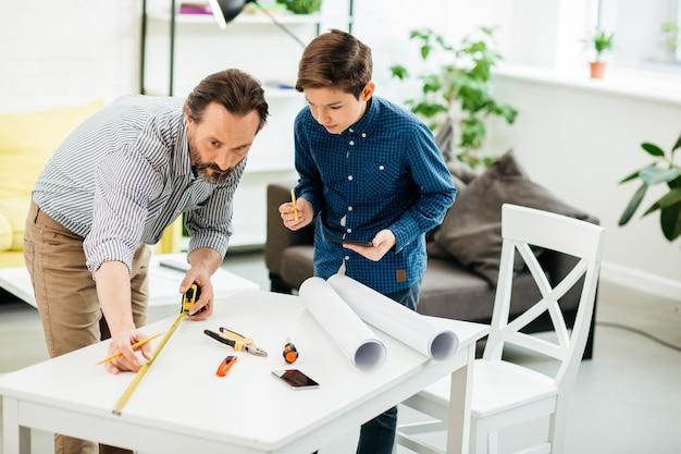 テーブルの横に巻尺を持って立っている穏やかなひげを生やした中年の男性と彼の息子は鉛筆とタブレットを持ってそれを見ています