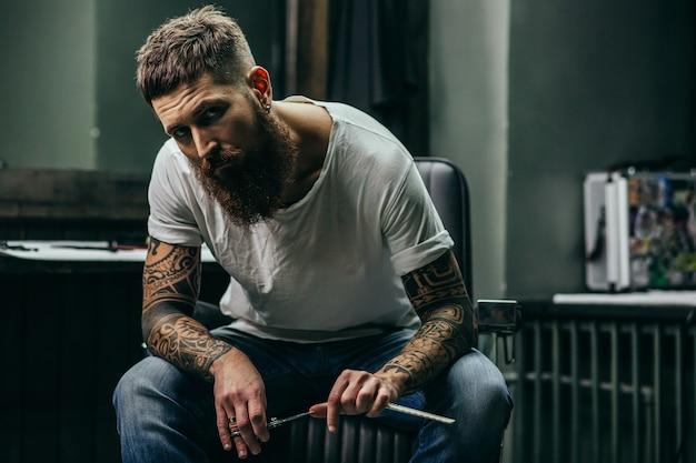 안락의 자에 앉아 면도칼을 들고 찡그린 수염을 한 문신을 한 남자