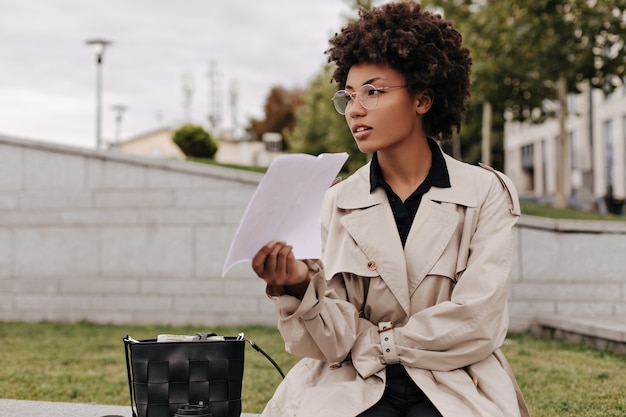 Calm beautiful brunette woman in beige trench coat and eyeglasses holds white paper sheet and sits outdoors