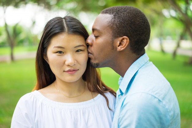 Calm beautiful chinese girl feeling kiss of boyfriend and looking at camera.