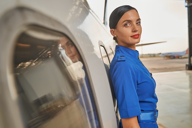 Calm beautiful female flight attendant standing with her back to the fuselage of a plane and smiling