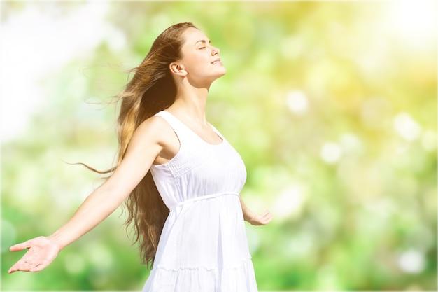 포니테일로 야외에서 신선한 공기를 즐기고 있는 차분하고 아름다운 미소를 짓고 있는 젊은 여성,